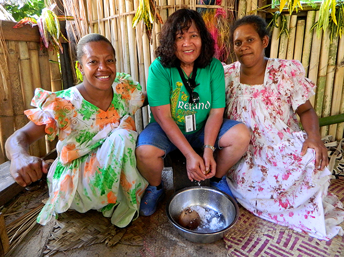 June Keitadi (left) and Del Abcede grating coconut on Aneityum Island on Christmas Day 2015. Photo by David Robie