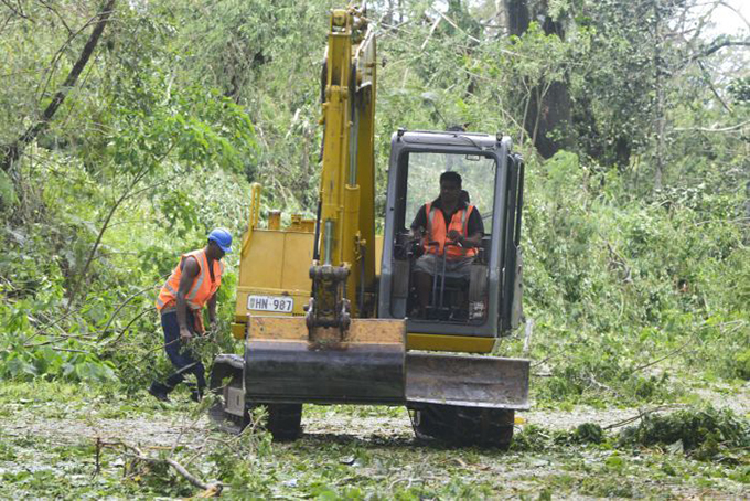A bulldozer clearing trees off a road near Suva. Image: Joe Yaya