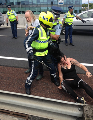 A police pulls a protester by the hair during the Auckland demonstration. Image: The Daily Blog