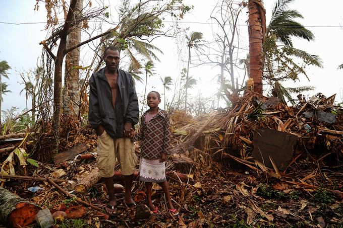 A ni-Vanuatu father and daughter stand in the wreckage of their home after Cyclone Pam. Image: UNICEF/Further Arts