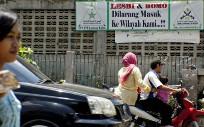People negotiate the traffic past a banner put up by the hardline Islamic Defenders Front calling for gay people to leave the Cigondewah Kaler area in Bandung, West Java, Indonesia. Image: Antara Foto