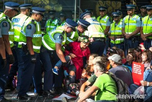 Police remove a climate action protester from in front of the oil industry conference at Auckland's Sky City. Image: Greenpeace Live Newsfeed