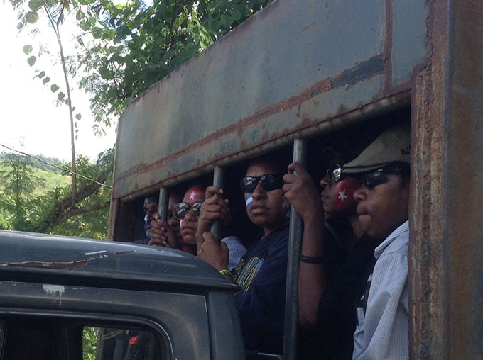 Arrested Papuan protesters behind bars on a police truck in Jayapura. Image: Tabloid Jubi