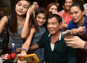 Philippines' President-elect Rodrigo Duterte poses for selfie pictures with supporters at his first media conference after winning the presidential election. Image: Philippine Daily Inquirer