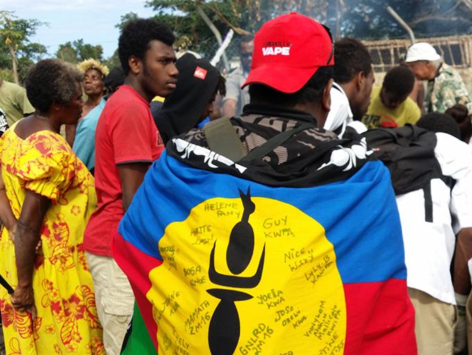 A Kanak wearing the Kanak flag watching a fire making demonstration at Tupunis. Image: David Robie/PMC