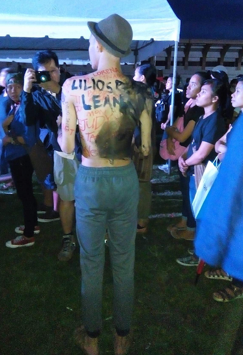 The shirtless young Filipino has names written on his back - victims of the Marcos dictatorship. Image: Becky Horton
