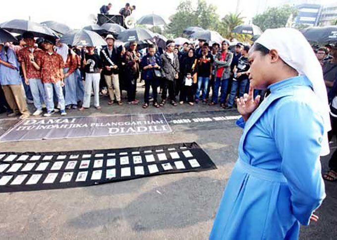 A nun observes photographs of victims of past human rights abuses in front of the State Palace in Jakarta during a weekly rally that is locally known as Kamisan. This rally was the 417th since 2007 and it demanded demanding the government resolve the cases. (Seto Wardhana )