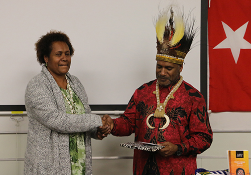 AUT doctoral student Stephanie Sageo-Tupungu of Papua New Guinea makes a presentation to Benny Wenda on behalf of the Pacific Media Centre. Image: Kendall Hutt/PMC