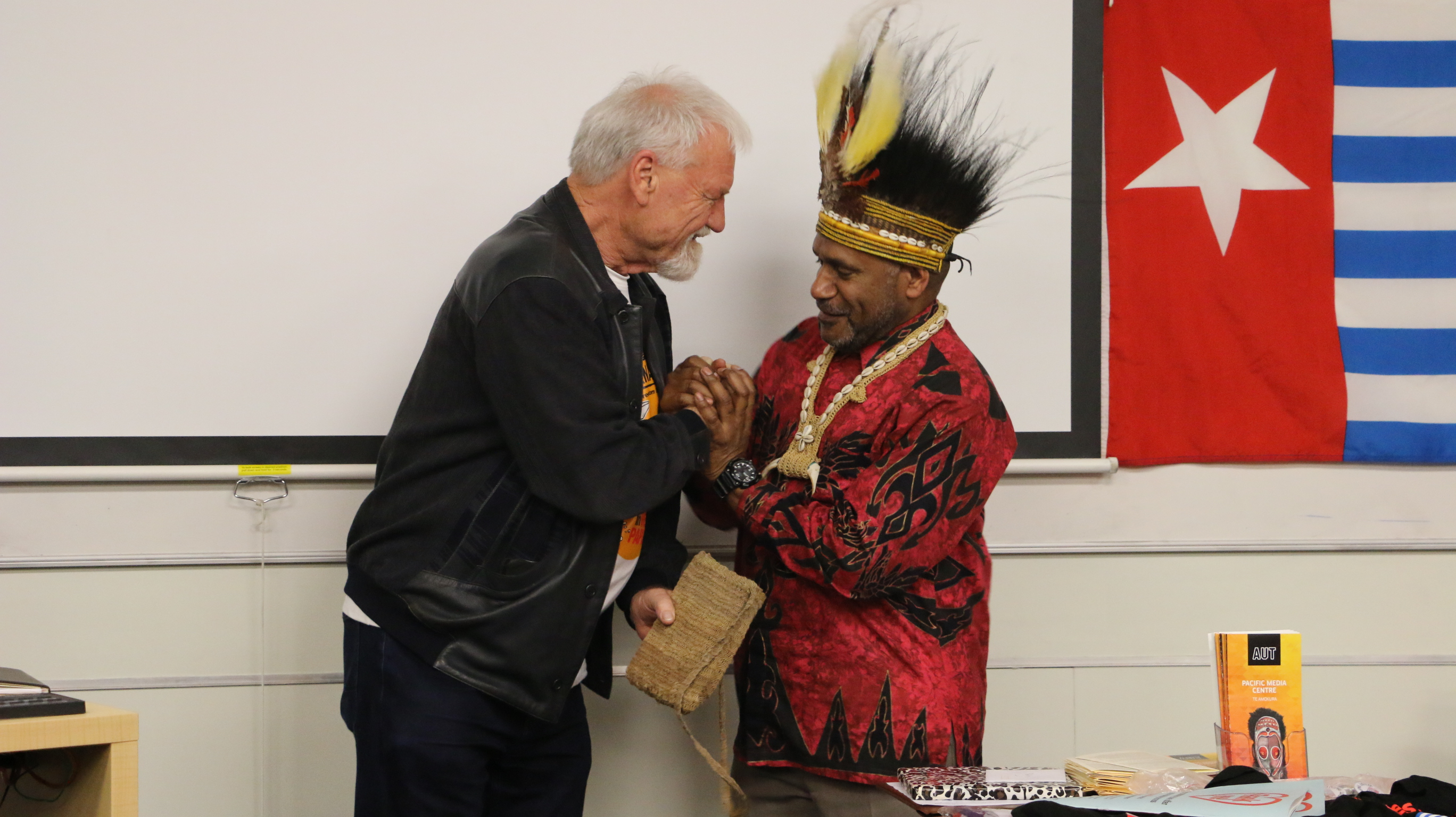 "Free West Papua advocate Benny Wenda presents Pacific Media Centre Professor David Robie with a traditional ""bilum"" for his journalism about West Papuan freedom. Image: Kendall Hutt/PMC"