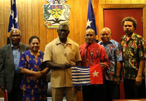 Full support … West Papuan Independence leader Benny Wenda (in red shirt) holds the banned West Papuan Morning Star flag with key supporter Solomon Islands Prime Minister Manasseh Sogavare during his visit last year. Image: bennywenda.org