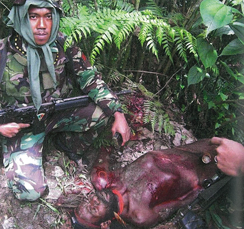 "A ""trophy photo"" by an Indonesian soldier from Battalion 753 of a man he had shot from the Lani tribe in 2010. Image from Papua Blood"