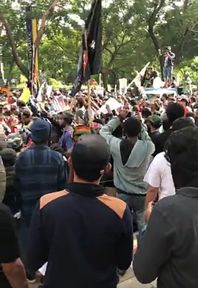 "A scene from the Surabaya rally today with the crowd chanting ""Freedom Papua"". The men in the front of the image appear to be undercover police filming and recording events. A short distance away there was a counterprotest with Indonesian flags. Police kept the two groups apart. Image: Still from a West Papuan sourced video"