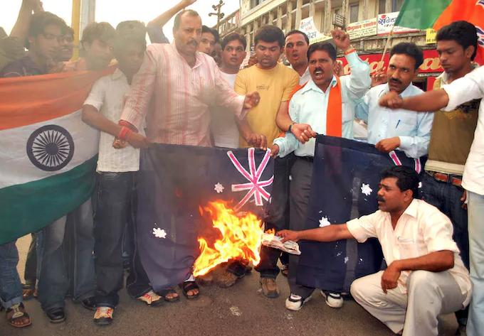 Protesters burn an Australian flag