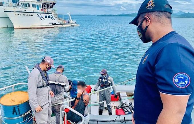A Fiji Navy crewman hands over the survivors