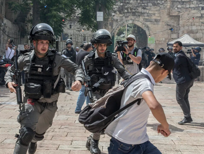 sraeli police chase a Palestinian demonstrator