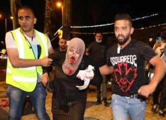 People helping an injured Palestinian woman