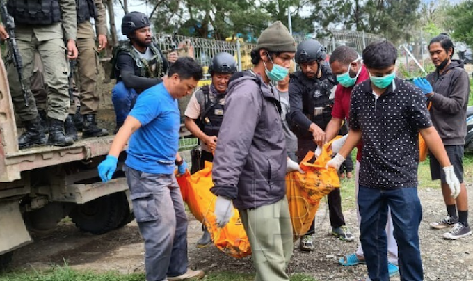 Indonesian police carry a body in the current crackdown near Timika, Papua.